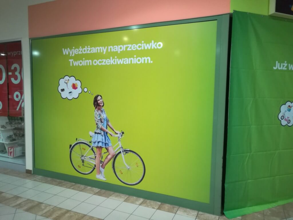 Witryna oklejona zieloną reklamą